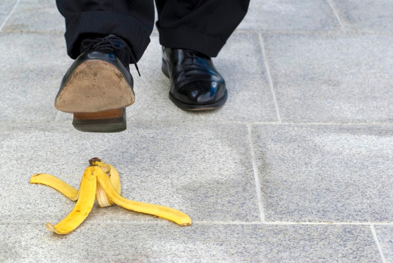 Uomo che pesta una buccia di banana